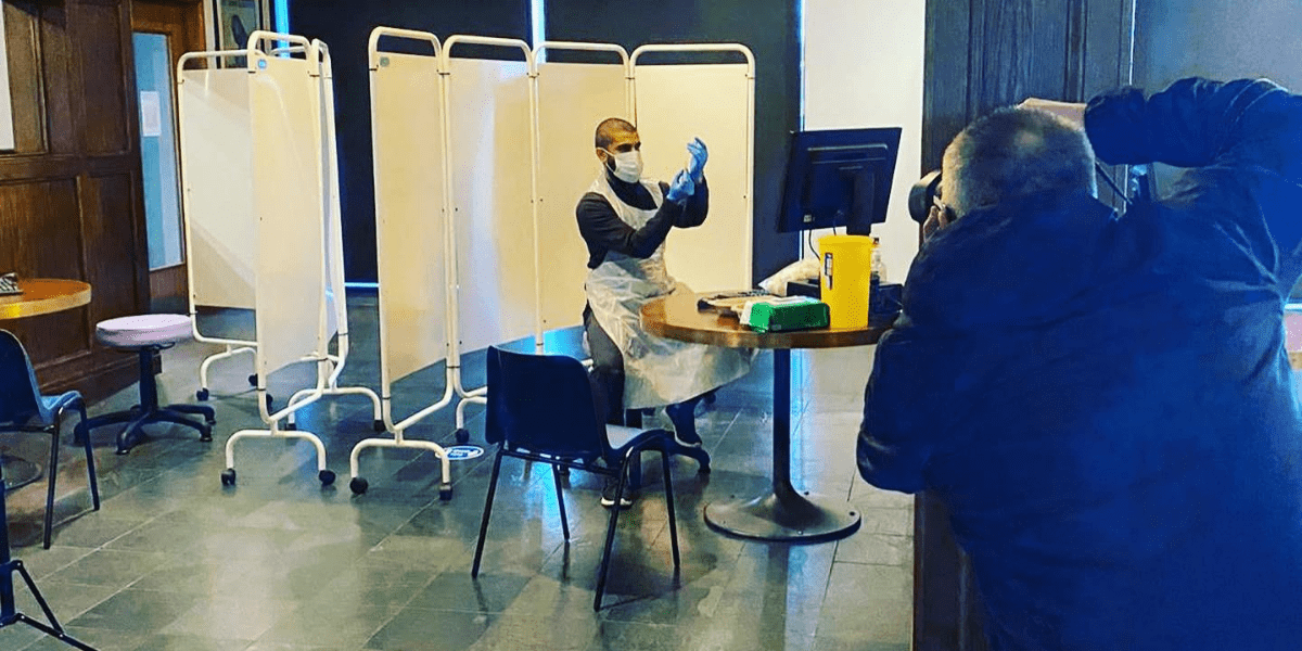 Pharmacist holding syringe in vaccination centre